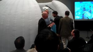"Dr. Roger Kneebone addressing attendees while ""igloo"" is being closed and sim players prepare a case presentation."